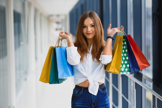 モールの背景の上の買い物袋を持つ若い女性の笑顔