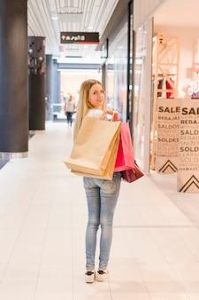 쇼핑 가방 쇼핑몰에 서있는 젊은 여자를 웃 고