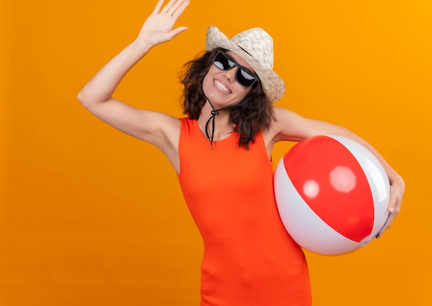A smiling young woman with short hair in an orange shirt wearing sun hat and sunglasses holding inflatable ball showing goodbye