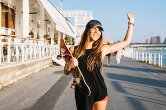 Smiling young woman with skateboard raising her arms while walking on street