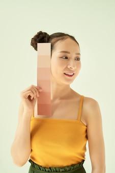 明るい背景の上に立っている間、肌のトーンパレットまたはサンプルで若い女性を笑顔
