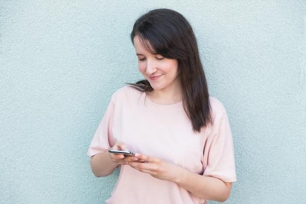 壁の背景にスマートフォンで若い女性の笑顔