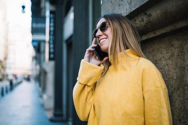 Улыбается молодая женщина с солнцезащитные очки и смартфон возле здания на улице