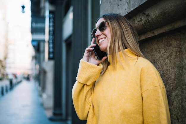 Smiling young woman with sunglasses and smartphone near building on street