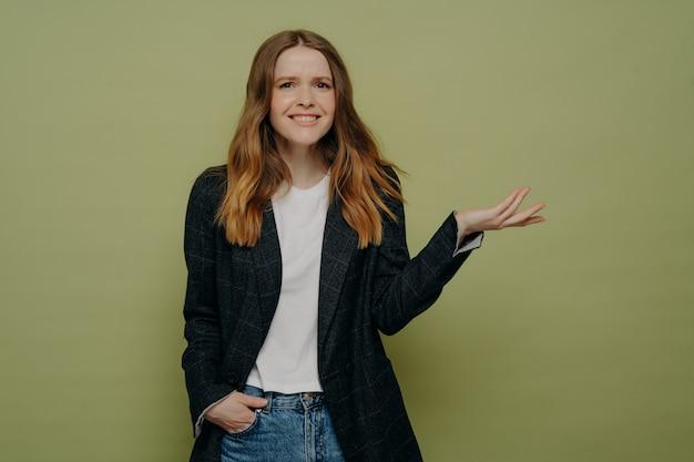 한 손을 주머니에 넣고 회색 스튜디오 벽에 고립된 채 어두운 정장 재킷, 흰색 상의, 청바지를 입은 채 손을 기울이고 있는 웃고 있는 젊은 여성