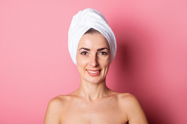Smiling young woman with towel on head, nude shoulders on pink background.