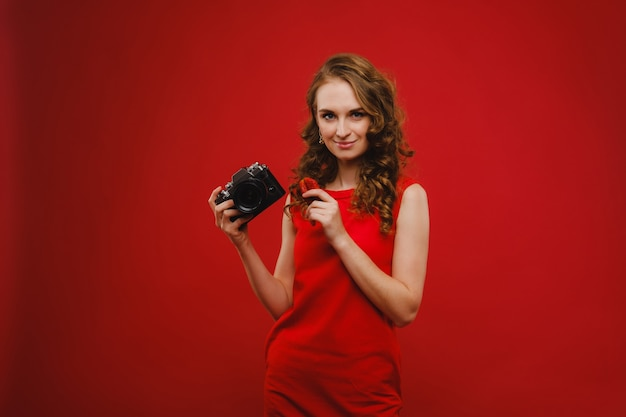 A smiling young woman with wavy hair holds a strawberry and photographs it, holding a delicious fresh strawberry