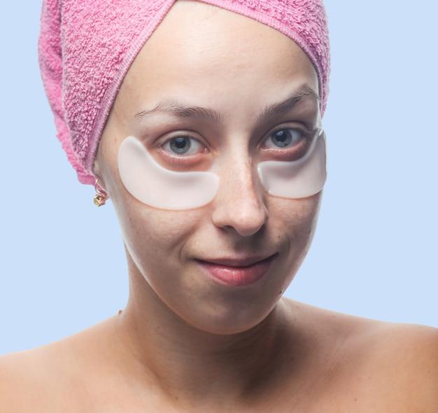 目の下の白いパッチと青に分離された彼女の頭の上のピンクのタオルで若い女性の笑顔。クローズアップの肖像画。スキンケア