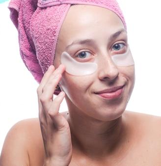 目の下の白いパッチと白で隔離される彼女の頭の上のピンクのタオルを持つ若い女性の笑顔。クローズアップの肖像画。スキンケア
