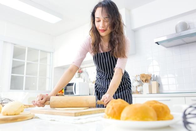 笑顔の若い女性は、キッチンで甘いパイやペストリー生地を作る木製のローラーピン、家族の夕食やデザートのベーキングパンを準備するエプロンで料理する幸せな千年紀の女性を愛する妻と一緒に仕事をします