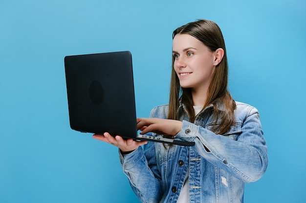 Smiling young woman working on laptop pc