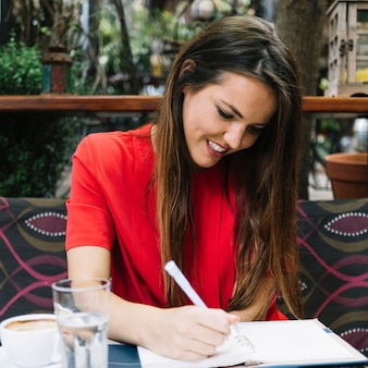 Smiling young woman writing schedule in diary