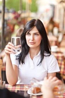 Улыбающиеся молодые женщины в кафе, пьющие белое вино. концепция общения и дружбы.