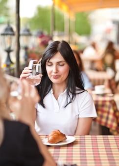 Улыбающиеся молодые женщины в кафе пьют белое вино или воду. концепция общения и дружбы.