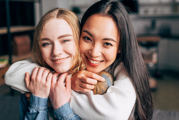 Smiling young women embracing at home