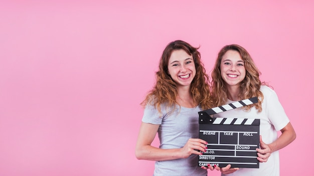 Smiling young women holding clapper board in hands against pink backdrop