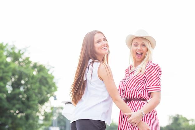 야외에서 재미를 만드는 서로의 손을 잡고 웃는 젊은 여성