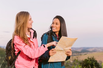 Smiling young women holding map