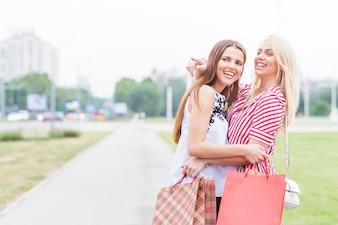 Smiling young women holding shopping bag standing in garden