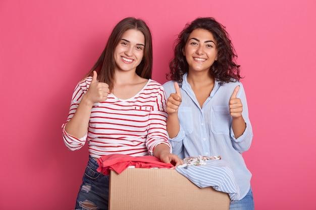 Улыбающиеся молодые женщины позируют возле коробки, полной одежды