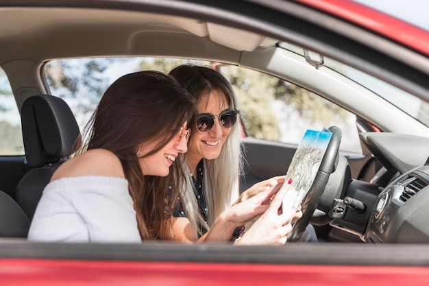 Smiling young women sitting in car looking at map