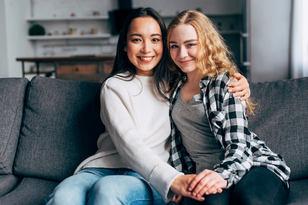 Smiling young women sitting on couch together