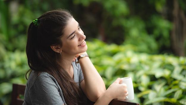 笑顔の若い女性は家にいます