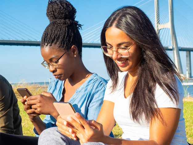 Smiling young women using smartphones in park