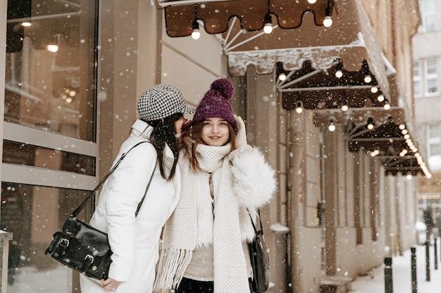暖かい冬の服を着てチャットしている若い女性の笑顔