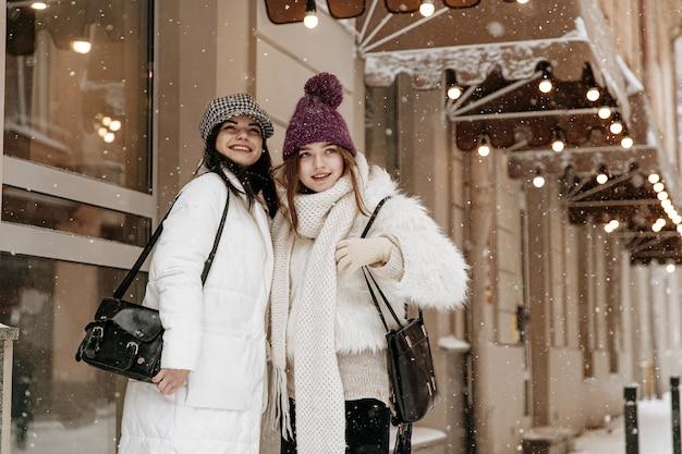 Улыбающиеся молодые женщины в теплой зимней одежде болтают