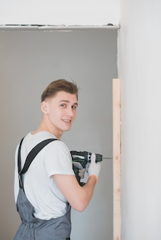 Smiling young working man in overalls drills screws with an electric screwdriver in an apartment
