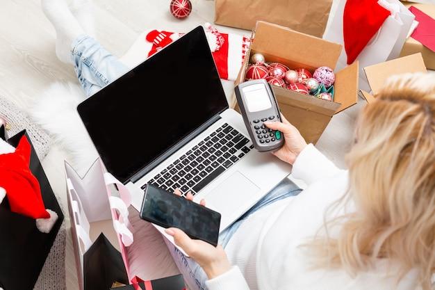 스웨터를 입은 웃고 있는 젊은 여성은 신용 카드 결제를 처리하고 받기 위해 은행 결제 단말기를 들고 있습니다. 새 해 복 많이 받으세요 축 하 메리 홀리데이 개념