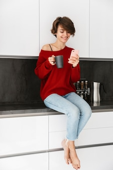 Smiling younh woman wearing sweater sitting on a kitchen table at home, using mobile phone