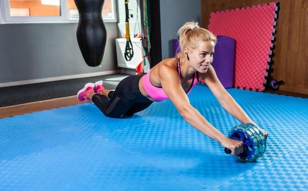 피트니스 수업에서 ab 롤러 복부 운동을 하는 웃고 있는 강한 피트니스 여성. 슬리밍 개념, 건강한 라이프 스타일