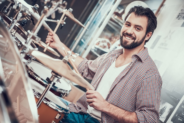 Smilling bearded man in shirt plays on drum set.