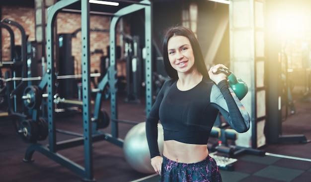 Улыбчивая брюнетка одной рукой поднимает гирю и смотрит в камеру в спортзале. силовые тренировки со свободными весами, функциональные тренировки