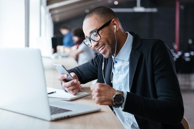 オフィスのラップトップの前にスマートフォンで陽気なビジネスマンのテキストメッセージを微笑む