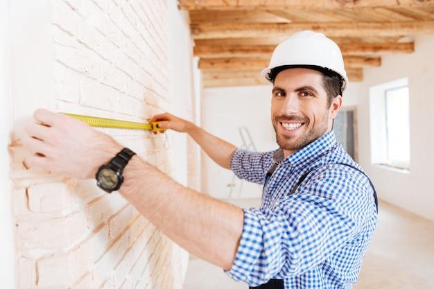 新しい家で巻尺を使用して製粉建設労働者