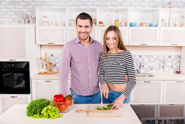 台所で野菜を切るのが大好きな微笑むカップル