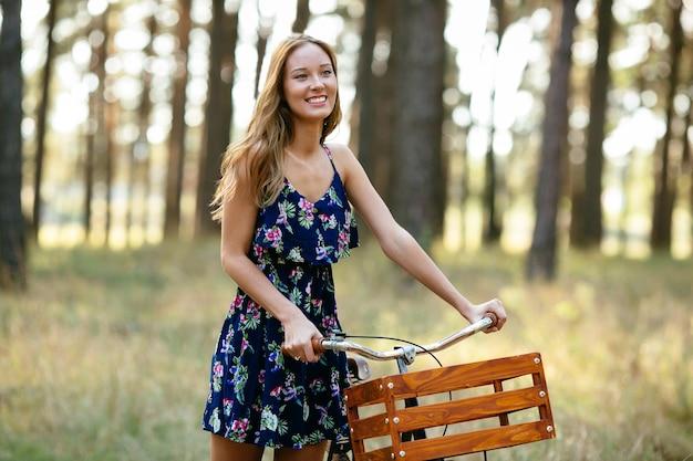 Улыбающаяся девушка с велосипедом в лесу.