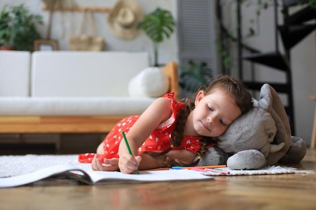 暖かい床に横たわっている幸せな女の子を微笑んで、彼女の近くにおもちゃの象が創造的な活動を楽しんでいる、アルバムの絵を着色する鉛筆を描く