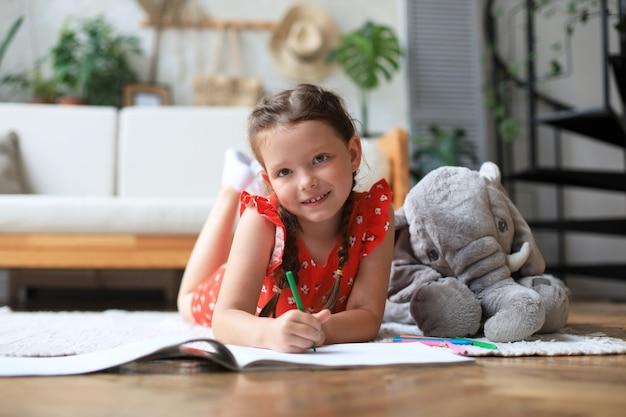 暖かい床に横たわっている幸せな女の子を微笑んで、近くにおもちゃの象がいて、創造的な活動を楽しんでいます。アルバムに絵を描く鉛筆を描いています。