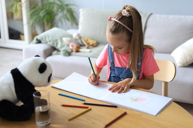 おもちゃのパンダのクマと一緒にテーブルに座って創造的な活動を楽しんでいる幸せな女の子を微笑んで、アルバムの絵を着色する鉛筆を描きます。