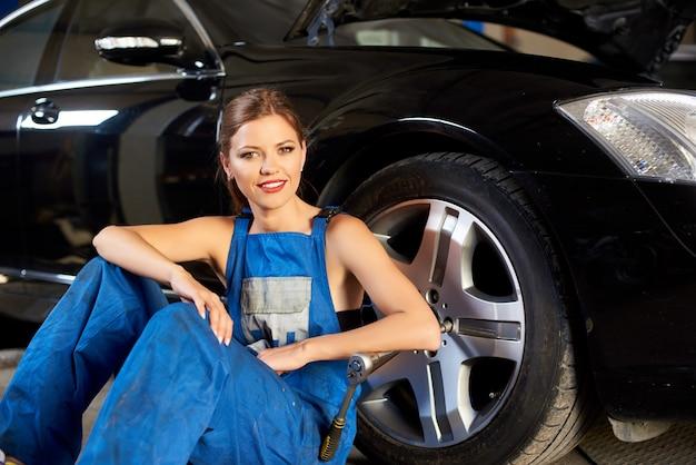 Smillingメカニックの女の子は黒い車のホイールの近くに座っています。