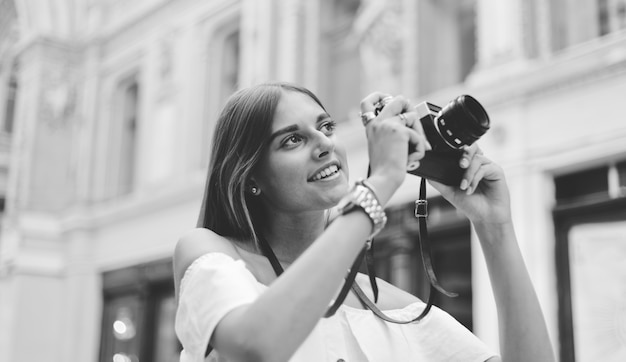Улыбающаяся красивая женщина с ретро камерой в руках, снимая городскую старую архитектуру. открывайте новые места. черное и белое