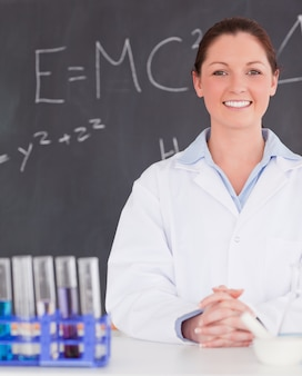 Smilling scientist stanting in front of a blackboard