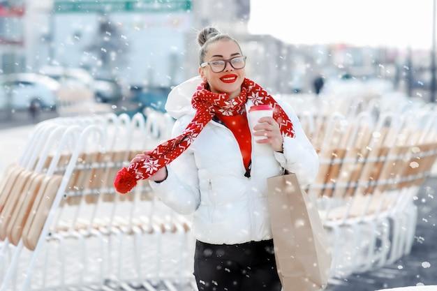 Улябающиеся зимняя девушка в теплой вязаной шапке и варежки, держа чашку в руках.