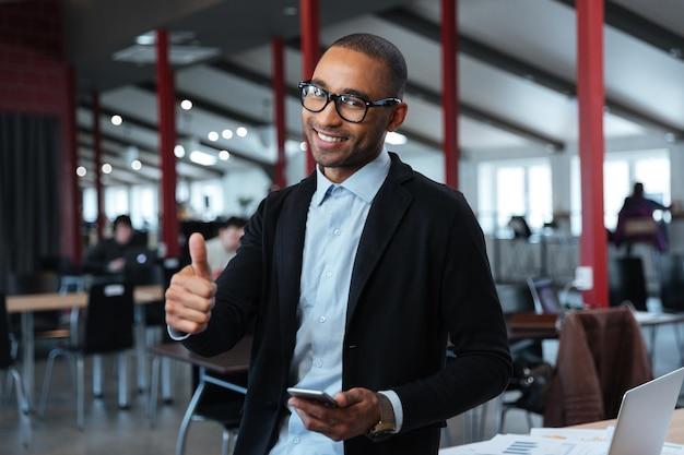 Улыбающийся молодой бизнесмен показывает нормальный знак в офисе