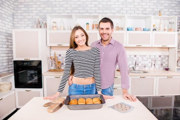 焼きたてのケーキとキッチンで恋に恋をしている若いカップルを微笑む