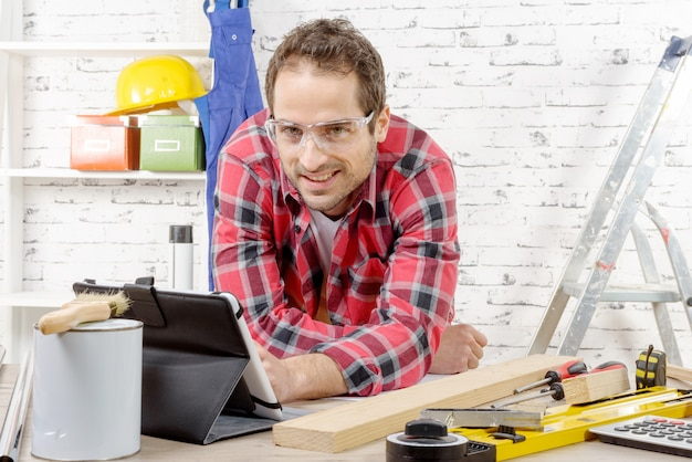Smilling young man using the tablet for diy